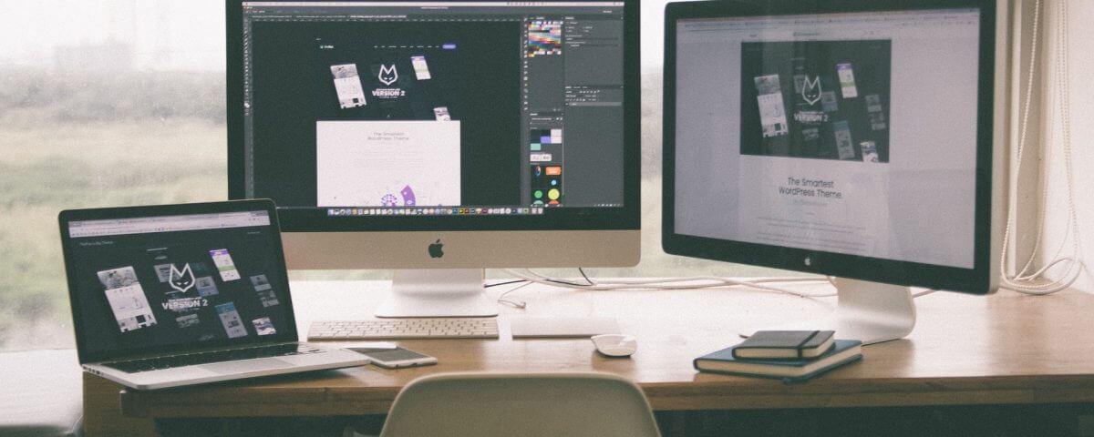 Bild: Schreibtisch mit einem Laptop und 2 Bildschirmen